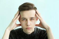 Framsida för ung man med handen och huvudvärk arkivfoton
