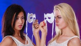 Framsida för två kvinnor med venetian maskeringar för karneval Arkivfoto