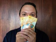 framsida med sinnesrörelseuttryck av en ung man med schweiziska sedlar royaltyfri foto