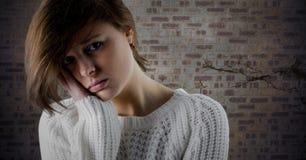 Framsida och huvud för kvinna ledsen i hand mot den bruna tegelstenväggen Royaltyfri Foto