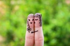 Framsida som målas på fingrarna kvinnan kysser hans flickvän på kind Arkivfoton