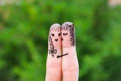 Framsida som målas på fingrarna kvinnan kysser hans flickvän på kind Royaltyfri Foto