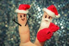 Framsida som målas på fingrarna Santa Claus ger gåvor Arkivbilder