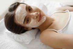 Framsidahudomsorg Härlig kvinna med den ansikts- kosmetiska maskeringen på Spa Royaltyfri Foto