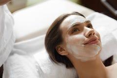 Framsidahudomsorg Härlig kvinna med den ansikts- kosmetiska maskeringen på Spa Arkivbild