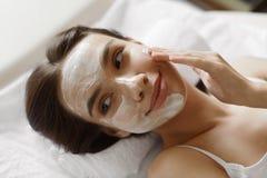 Framsidahudomsorg Härlig kvinna med den ansikts- kosmetiska maskeringen på Spa Arkivfoto
