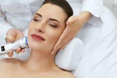Framsidahudomsorg Kvinna som gör blå ljus terapi på skönhetkliniken royaltyfri foto