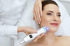 Framsidahudomsorg Kvinna som gör blå ljus terapi på skönhetkliniken royaltyfri bild