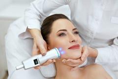 Framsidahudomsorg Kvinna som gör blå ljus terapi på skönhetkliniken royaltyfria foton