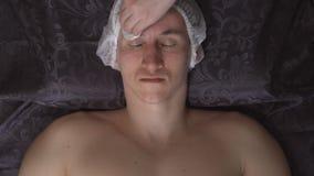 Framsidalokalvård Man i brunnsortsalong på tillvägagångssätt stock video