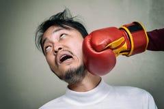 Framsidaman som får stansmaskin i framsida med boxninghandsken mot G Arkivfoton