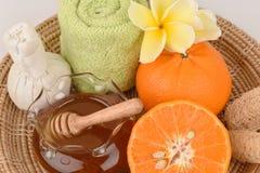 Framsidamaskering med apelsinen och honung som slätar hud och akne för blekmedel ansikts- Arkivbilder