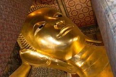 Framsidan av den guld- Buddhastatyn för vila på Wat-Po, Bangkok Arkivbilder