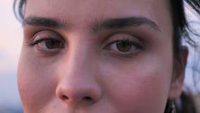 Framsidan av den härliga flickan är på taket av byggnad i sommar på solnedgång, stängda ögon som håller ögonen på på kameran, kop lager videofilmer