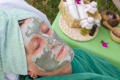 Framsidan av den höga kvinnan täckas av den ansikts- leramaskeringen Royaltyfri Foto