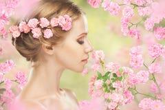 Framsidan av den unga härliga kvinnan med rosa färger blommar i hennes hår Fotografering för Bildbyråer