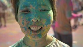 Framsidan av den unga lyckliga asiatiska flickan ler med färgglat pulver på holifestival i dag i sommar, färgbegrepp