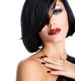 Framsidan av en kvinna med härligt mörker spikar och sexiga röda kanter Arkivfoto