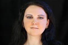 Framsidan av en ung brunett som ler med ljus makeup av ?gonen och kanter med guld-, mousserar arkivfoto