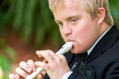 Framsidaskott av den rörelsehindrade pojken som spelar flöjten. Arkivbilder