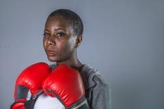 Framsidastående av den unga ilskna och utmanande svarta afro amerikanska sportkvinnan i boxninghandskar som utbildar och poserar  fotografering för bildbyråer