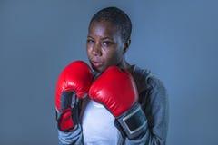 Framsidastående av den unga ilskna och utmanande svarta afro amerikanska sportkvinnan i boxninghandskar som utbildar och poserar  arkivbilder