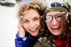 Framsidor av två unga kvinnor stängs upp med snö Arkivbilder