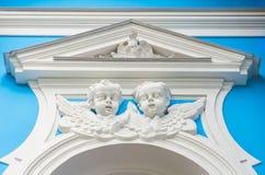 Framsidorna av änglarna ovanför stuckaturfönstret på den kyrkliga väggen Royaltyfri Bild