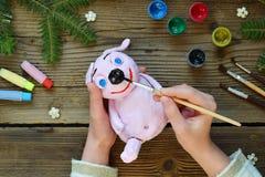 Framställning av det rosa svinet, symbol av 2019 Måla lera leka med gouachen Idérik fritid för barn Handgjorda hantverk på ferie  arkivbild