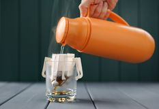 Framställning av droppandekaffe Hällande varmvatten från termoset in i exponeringsglas Arkivfoto