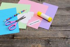 Framställning av ett julhälsningkort moment Den kulöra pappersuppsättningen, sax, blyertspennan, trädmallen, limpinne, glad jul ö Arkivbild
