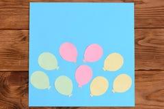 Framställning av ett kort med pappers- luftballonger moment Kurs för barn Kort med pappers- luftballonger på en trätabell Royaltyfria Bilder
