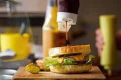 Framställning av läckra hemlagade Maxi Burger med grillad nötköttbiff, grönsallat, ost, tomat, lök, grillfestsås, honungsenap, ha Royaltyfri Fotografi