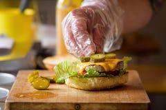 Framställning av läckra hemlagade Maxi Burger med grillad nötköttbiff, grönsallat, ost, tomat, lök, grillfestsås, honungsenap, ha Arkivbilder