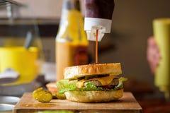 Framställning av läckra hemlagade Maxi Burger med grillad nötköttbiff, grönsallat, ost, tomat, lök, grillfestsås, honungsenap, ha Arkivfoto