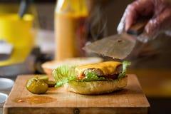 Framställning av läckra hemlagade Maxi Burger med grillad nötköttbiff, grönsallat, ost, tomat, lök, grillfestsås, honungsenap, ha Arkivbild