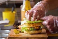 Framställning av läckra hemlagade Maxi Burger med grillad nötköttbiff, grönsallat, ost, tomat, lök, grillfestsås, honungsenap, ha Royaltyfri Bild