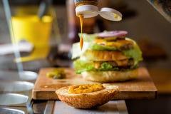 Framställning av läckra hemlagade Maxi Burger med grillad nötköttbiff, grönsallat, ost, tomat, lök, grillfestsås, honungsenap, ha Royaltyfria Foton