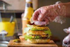 Framställning av läckra hemlagade Maxi Burger med grillad nötköttbiff, grönsallat, ost, tomat, lök, grillfestsås, honungsenap, ha Fotografering för Bildbyråer