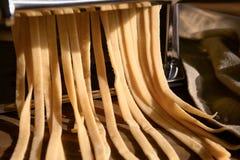 Framställning av tagliatelle med pastamaskinen, closeup arkivbilder
