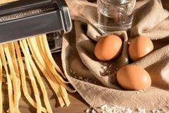 Framställning av tagliatelle med pastamaskinen på tabellen arkivfoton