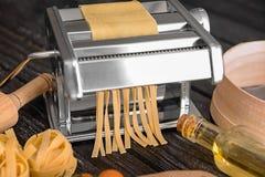 Framställning av tagliatelle med pastamaskinen på tabellen royaltyfria bilder