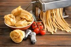 Framställning av tagliatelle med pastamaskinen på tabellen arkivfoto