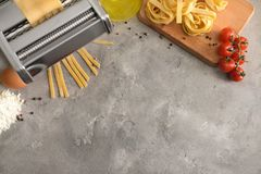 Framställning av tagliatelle med pastamaskinen på tabellen arkivbilder