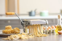 Framställning av tagliatelle med pastamaskinen på tabellen i kök arkivfoto