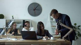 Framstickande som ger beställningar och arbetsuppgift till kvinnlig anställd arkivfilmer