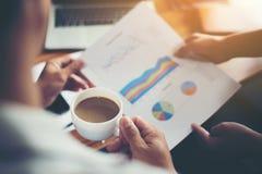 Framstickande som rymmer ett kopp kaffearbete med sekreteraren om analys Royaltyfri Fotografi