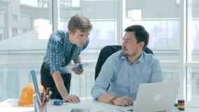 Framstickandet diskuterar projekt med anställd, ger rådgivning, genom att använda den digitala minnestavlan i nytt modernt kontor lager videofilmer
