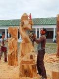 Framställning av träskulpturer med hjälpen av en yxa och en såg Royaltyfri Bild