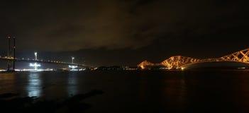 Framåt väg- och stångbro vid natt Arkivfoto